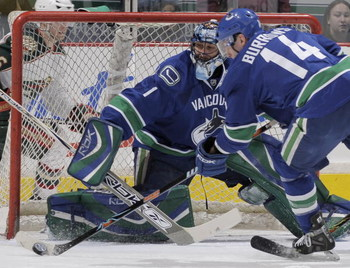 VANCOUVER, CANADA - MARCH 17:  Left wing Alex Burrows #14 of the Vancouver Canucks clears the puck from infront of goalie Roberto Luongo #1 of the Vancouver Canucks during their game against the Minnesota Wild at General Motors Place on March 21, 2008 in