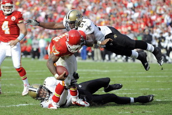 KANSAS CITY, MO - NOVEMBER 16:  Larry Johnson #27 of the Kansas City Chiefs is stopped by Scott Fujita #55 and Jonathan Vilma #51 of the New Orleans Saints on November 16, 2008 at Arrowhead Stadium in Kansas City, Missouri.  (Photo by G. Newman Lowrance/G