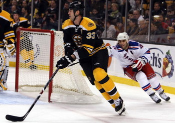 BOSTON - JANUARY 31:  Zdeno Chara #33 of the Boston Bruins tries to keep the puck from Scott Gomez #19 of the New York Rangers on January 31, 2009 at the TD Banknorth Garden in Boston, Massachusetts.  (Photo by Elsa/Getty Images)