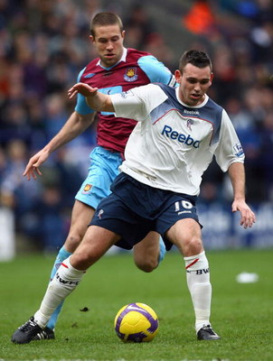 BOLTON, UNITED KINGDOM - FEBRUARY 21:  Mark Davies of Bolton Wanderers holds off a challenge from Matthew Upson of West Ham United during the Barclays Premier League match between Bolton Wanderers and West Ham United at the Reebok Stadium on February 21,