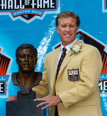 CANTON, OH - AUGUST 8:  Pro Football Hall of Fame enshrinee John Elway poses with his bust during the 2004 NFL Hall of Fame enshrinement ceremony August 8, 2004 in Canton, Ohio.  (Photo by David Maxwell/Getty Images)