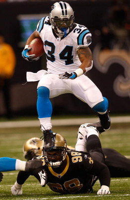 NEW ORLEANS - DECEMBER 28:  DeAngelo Williams #34 of the Carolina Panthers jumps over Sedrick Ellis #98 of the New Orleans Saints on December 28, 2008 at the Superdome in New Orleans, Louisiana.  (Photo by Chris Graythen/Getty Images)