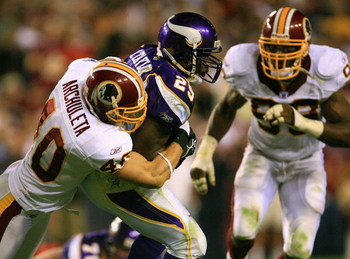 LANDOVER, MD - SEPTEMBER 11: Chester Taylor #29 of the Minnesota Vikings gets tackled by Adam Archuleta #40 from the Washington Redskins on the first Monday Night Football game of the season on September 11, 2006 at FedEx Field in Landover, Maryland. The