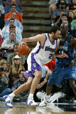 SACRAMENTO, CA - MAY 12:  Vlade Divac #21 of the Sacramento Kings drives around Kevin Garnett #21 of the Minnesota Timberwolves in Game four of the Western Conference Semifinals during the 2004 NBA Playoffs at Arco Arena on May 12, 2004 in Sacramento, Cal