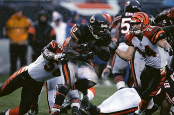 CHICAGO - SEPTEMBER 25:  Thomas Jones #20 of the Chicago Bears carries the ball against Brian Simmons #56 and Kevin Kaesviharn #34 of the Cincinnati Bengals on September 25, 2005 at Soldier Field in Chicago, Illinois. The Bengals defeated the Bears 24-7.