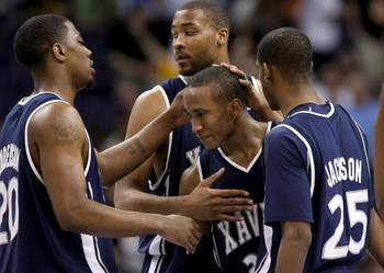 PHOENIX - MARCH 29:  Stanley Burrell #34 of the Xavier Musketeers is congratulated by teammates C.J. Anderson #20, Jason Love #31 and Dante' Jackson #25 as Burrell leaves the game in final minute of the West Regional Final for the last time as a Muskateer