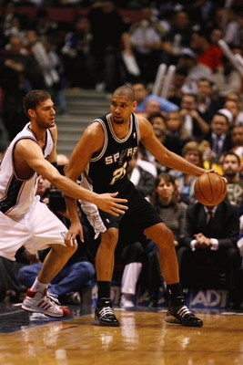 EAST RUTHERFORD, NJ - FEBRUARY 10:  Tim Duncan #21 of the San Antonio Spurs dribbles against Brook Lopez #11 of The New Jersey Nets during their game on February 10, 2009 at The Izod Center in East Rutherford, New Jersey.  NOTE TO USER: User expressly ack