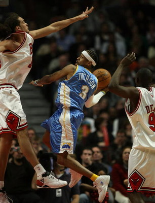 CHICAGO - FEBRUARY 22: Allen iverson #3 of the Denver Nuggets leaps to pass the ball between Joakim Noah #13 (L) and Luol Deng #9 of the Chicago Bulls on February 22, 2008 at the United Center in Chicago, Illinois. NOTE TO USER: User expressly acknowledge