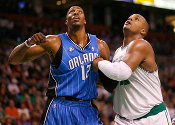 BOSTON, MA - MARCH 8:  Glen David #11 of the Boston Celtics battles Dwight Howard #12 of Orlando Magic for a rebound at the TD Banknorth Garden on March 8, 2009 in Boston, Massachusetts. The magic won 86-79. NOTE TO USER: User expressly acknowledges and a