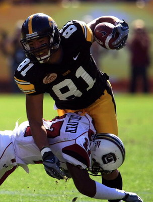 TAMPA, FL - JANUARY 01:  Tony Moeaki #81 of the Iowa Hawkeyes runs upfield as he fights off the tackle of Chris Culliver #17 of the South Carolina Gamecocks during the Outback Bowl on January 1, 2009 at Raymond James Stadium in Tampa, Florida.  (Photo by