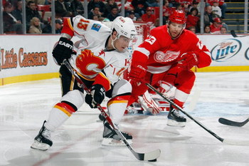 DETROIT - DECEMBER 10:  Mike Cammalleri #13 of the Calgary Flames skates with the puck against Brad Stuart #23 of the Detroit Red Wings at Joe Louis Arena December on 10, 2008 in Detroit, Michigan. (Photo by Dave Sandford/Getty Images)