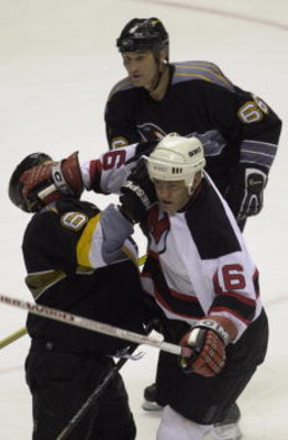 15 May 2001:  Bobby Holik #16 of the New Jersey Devils and Bob Boughner #6 of the Pittsburgh Penguins collide as Mario Lemieux #66 follows the play in game two of the Eastern Conference Finals of the 2001 Stanley Cup Playoffs at the Continental Airlines A