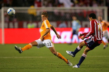 CARSON, CA - OCTOBER 20: Stuart Holden #22 of Houston Dynamo tries to get a foot on the ball as Orlando Perez #77 of CD Chivas USA clears the ball in the first half during their MLS match at the Home Depot Center October 20, 2007 in Carson, California.  (