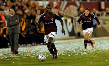 COMMERCE CITY, CO - MARCH 29:  Omar Cummings #14 of the Colorado Rapids controls the ball and heads upfield as head coach Fernando Clavijo (L) and teammate Terry Cooke #11 trail the play during the MLS soccer game against the Los Angeles Galaxy at Dick's 