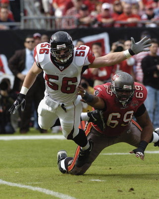 Atlanta Falcons linebacker Keith Brooking flies over Tampa Bay Buccaneers  tackle Anthony Davis  December 24, 2005 in Tampa.  The Bucs defeated the Falcons 27 - 24.  (Photo by Al Messerschmidt/Getty Images)