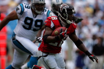 CHARLOTTE, NC - SEPTEMBER 10:  Running back Warrick Dunn #28 of the Atlanta Falcons evades defensive tackle Maake Kemoeatu #99 of the Carolina Panthers during their game on September 10, 2006 at Bank of America Stadium in Charlotte, North Carolina.  The F
