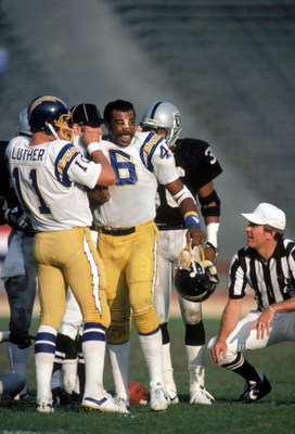 LOS ANGELES - DECEMBER 18:  Quarterback Ed Luther #11 of the San Diego Chargers tucks the shoulder pads into the jersey of teammate Chuck Muncie #46 during a game against the Los Angeles Raiders at the Los Angeles Memorial Coliseum on December 18, 1983 in