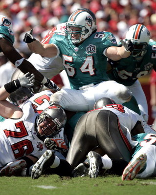 TAMPA, FL - OCTOBER 16:  Linebacker Zach Thomas #54 of the Miami Dolphins winds up on a pile of Tampa Bay Buccaneers defense on October 16, 2005 at Raymond James Stadium in Tampa, Florida.  (Photo by Eliot J. Schechter/Getty Images)