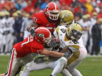 ATHENS, GA - NOVEMBER 29:  Defensive teammates Chad Gloer #17 and Akeem Dent #51 of the Georgia Bulldogs tackle running back Roddy Jones #20 of the Georgia Tech Yellow Jackets while Jones' teammate Marcus Wright #3 tries to block during the game at Sanfor
