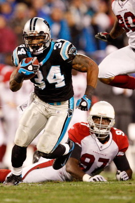 CHARLOTTE, NC - JANUARY 10:  DeAngelo Williams #34 of the Carolina Panthers runs the ball while Bryan Robinson #97 of the Arizona Cardinals looks on during the NFC Divisional Playoff Game on January 10, 2009 at Bank of America Stadium in Charlotte, North