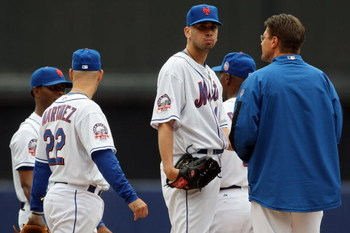 NEW YORK - SEPTEMBER 28:  Starting pitcher #46 Oliver Perez (center) of the New York Mets is visited by the trainer after feilding a hit with his pitching hand against the Florida Marlins during the last regular season baseball game ever played in Shea St
