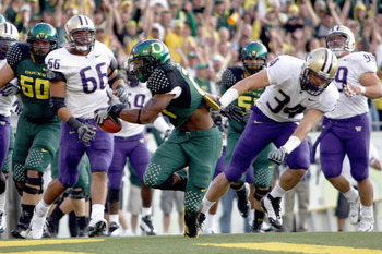 EUGENE, OR - AUGUST 30:  LaMichael James #21 of the Oregon Ducks carries the ball as he is grabbed by Tripper Johnson #34 of the Washington Huskies at Autzen Stadium on August 30, 2008 in Eugene, Oregon. (Photo by Jonathan Ferrey/Getty Images)