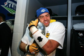 TAMPA, FL - FEBRUARY 01:  James Farrior #51 of the Pittsburgh Steelers hugs the Vince Lombardi trophy in the locker room after the Steelers won 27-23 against the Arizona Cardinals during Super Bowl XLIII on February 1, 2009 at Raymond James Stadium in Tam