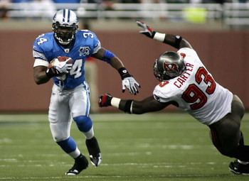 DETROIT - NOVEMBER 23:  Running back Kevin Smith #34 of the Detroit Lions carries the ball past Kevin Carter #93 of the Tampa Bay Buccaneers during the second quarter of the NFL game at Ford Field on November 23, 2008 in Detroit, Michigan.  (Photo by Chri