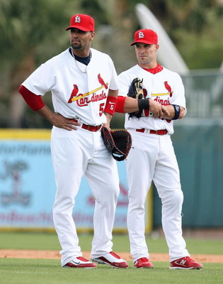 JUPITER, FL - FEBRUARY 25:  First baseman Albert Pujols #5 of the St. Louis Cardinals talks with second baseman Skip Schumaker #55 during a pitching change against the Florida Marlins during a spring training game at Roger Dean Stadium on February 25, 200