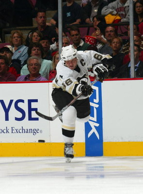 EAST RUTHERFORD, NJ - OCTOBER 5:  Mario Lemieux #66 of the Pittsburgh Penguins makes a pass from the blueline against the New Jersey Devils during their NHL opening night game at the Continental Airlines Arena on October 5, 2005 in East Rutherford, New Je