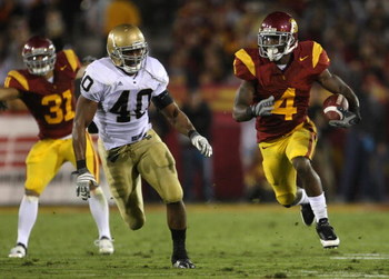 LOS ANGELES, CA - NOVEMBER 29:  Tailback Joe McKnight #4 of the USC Trojans is pursued by Maurice Crum #40 of the Notre Dame Fighting Irish during the game against at the Memorial Coliseum on November 29, 2008 in Los Angeles, California. USC defeated Notr