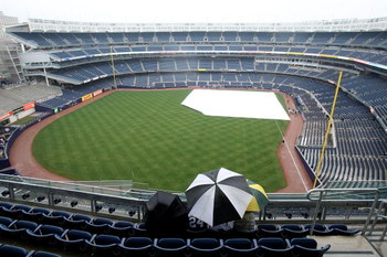 NEW YORK - APRIL 03:  Fans wait out the rain before the New York Yankees game against the Chicago Cubs at Yankee Stadium on April 3, 2009 in the Bronx borough of New York City.  (Photo by Ezra Shaw/Getty Images)