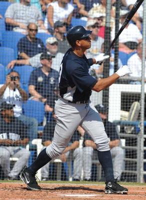 DUNEDIN, FL - FEBRUARY 25 :  Infielder Alex Rodriguez of the New York Yankees hits a two-run home run against the Toronto Blue Jays February 25, 2009 at Dunedin Stadium in Dunedin, Florida.  (Photo by Al Messerschmidt/Getty Images)