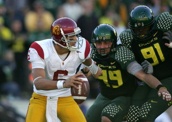 EUGENE, OR - OCTOBER 27:  Quarterback Mark Sanchez #6 of the Southern California Trojans is pressured by Nick Reed #49 and Ra'Shon Harris #91 of the Oregon Ducks at Autzen Stadium October 27, 2007 in Eugene, Oregon.  (Photo by Jonathan Ferrey/Getty Images