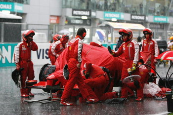 KUALA LUMPUR, MALAYSIA - APRIL 05:  Ferrari mechanics shelter their car during heavy rain during the Malaysian Formula One Grand Prix at the Sepang Circuit on April 5, 2009 in Kuala Lumpur, Malaysia.  (Photo by Paul Gilham/Getty Images)