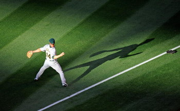 ANAHEIM, CA - APRIL 06:  Mark Ellis #14 of the Oakland Athletics throws the ball during pre game warm up against Los Angeles Angels of Anaheim on opening day at the Angel Stadium of Anaheim on April 6, 2009 in Anaheim, California.  (Photo by Kevork Djanse