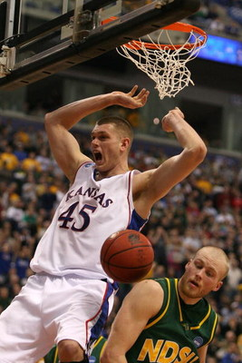 MINNEAPOLIS - MARCH 20:  Cole Aldrich #45 of the Kansas Jayhawks reacts after he dunked the ball over Michael Tveidt #23 (R) of the North Dakota State Bison during the first round of the NCAA Division I Men's Basketball Tournament at the Hubert H. Humphre