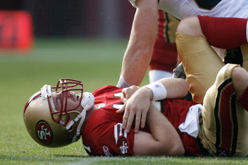 SAN FRANCISCO - OCTOBER 28:  Quarterback Alex Smith #11 of the San Francisco 49ers grimaces in pain and reaches for his shoulder during a game against the New Orleans Saints at Monster Park October 28, 2007 in San Francisco, California. New Orleans won 31