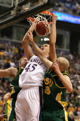 MINNEAPOLIS - MARCH 20:  Cole Aldrich #45 of the Kansas Jayhawks dunks against Michael Tveidt (R) #23 and Brett Winkelman #22 the North Dakota State Bison in the second half during the first round of the NCAA Division I Men's Basketball Tournament at the