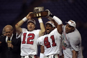 17 Jan 1999: Chris Chandler #12 of the Atlanta Falcons holds the trophy with Eugene Robinson #41 during the NFC Championship Game against the Minnesota Vikings at the H. H. H. Metrodome in Minneapolis, Minnesota. The Falcons defeated the Vikings 30-27. Ma