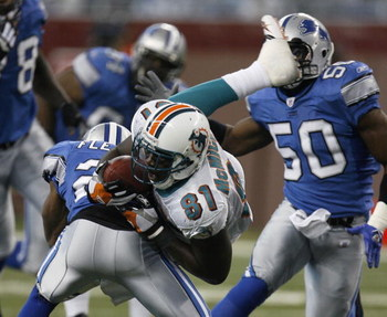 DETROIT - NOVEMBER 23:  Randy McMichael #81 of the Miami Dolphins is taken off his feat after a second quarter catch by Jamar Fletcher #21 of the Detroit Lions in front of Ernie Sims #50 on November 23, 2006 at Ford Field in Detroit, Michigan. (Photo By G