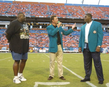 Former  Miami Dolphins  quarterback Dan Marino and offensive lineman Keith Simms (left) honor lineman Richmond Webb, who retired, August 21, 2004 in Miami.  (Photo by Al Messerschmidt/Getty Images)