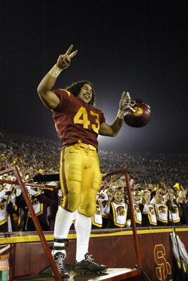 LOS ANGELES - NOVEMBER 30:  Safety Troy Polamalu #43 of Southern California leads his team's celebration from the bandleaders ladder after the game against Notre Dame on November 30, 2002 at the Los Angeles Coliseum in Los Angeles, California.  Southern C