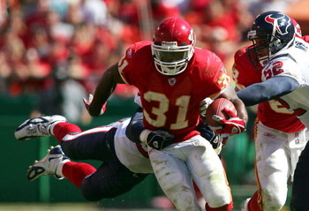 KANSAS CITY, MO - SEPTEMBER 26: Runningback Priest Holmes #31 of the Kansas City Chiefs breaks through the tackles of Jay Foreman #56 and Kailee Wong #52 of the Houston Texans as he scrambles under pressure during the 4th quarter of their NFL game on Sept