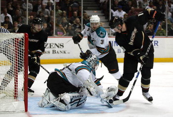 ANAHEIM, CA - MARCH 15:  Goaltender Evgeni Nabokov #20 of the San Jose Sharks and Corey Perry #10 of the Anaheim Ducks vie for the puck in the third period during their NHL game at Honda Center on March 15, 2009 in Anaheim, California.  (Photo by Victor D