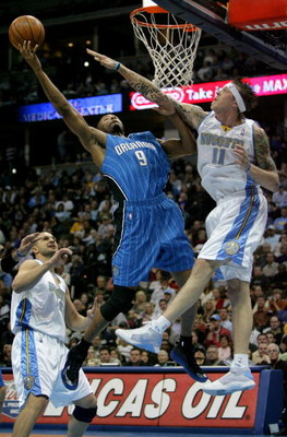 DENVER - JANUARY 17:  Rashard Lewis #9 of the Orlando Magic lays up a shot over the defense of Chris Andersen #11 of the Denver Nuggets during NBA action at the Pepsi Center on January 17, 2009 in Denver, Colorado. NOTE TO USER: User expressly acknowledge