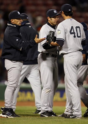 BOSTON - APRIL 11:  Chien Ming-Wang #40 of the New York Yankees is congratulated by Johnny Damon #18 and manager Joe Girardi #27 after Ming-Wang pitched a complete game on April 11, 2008 at Fenway Park in Boston, Massachusetts.  (Photo by Elsa/Getty Image