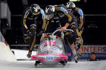 WHISTLER, BC - FEBRUARY 07:  Driver Karl Angerer of Germany and his crew push from the start in the first heat as they finished ninth in the men's four man bobsleigh finals at the FIBT Bobsleigh and Skeleton World Cup at the Whistler Sliding Center on Feb