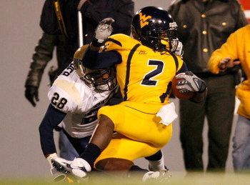 MORGANTOWN, WV - DECEMBER 1:  Defensive back Eric Thatcher # 28 of the Pittsburgh Panthers tackles receiver Darius Reynaud #2 of the West Virginia Mountaineers during the first half at Milan Puskar Stadium December 1, 2007 in Morgantown, West Virginia.  P