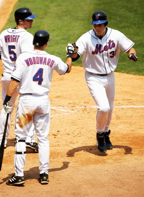 FLUSHING, NY -  AUGUST 4:  Mike Piazza #31 is congratulated by David Wright #5 and Chris Woodward #4 of the New York Mets after Piazza hit a two-run home run against the Milwaukee Brewers in the third inning at Shea Stadium on August 4, 2005 in Flushing,